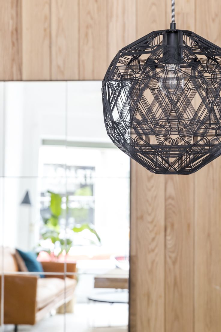 Close-up detail of the hanging Zattelite pendant in black, with a fine metallic geometric design.
