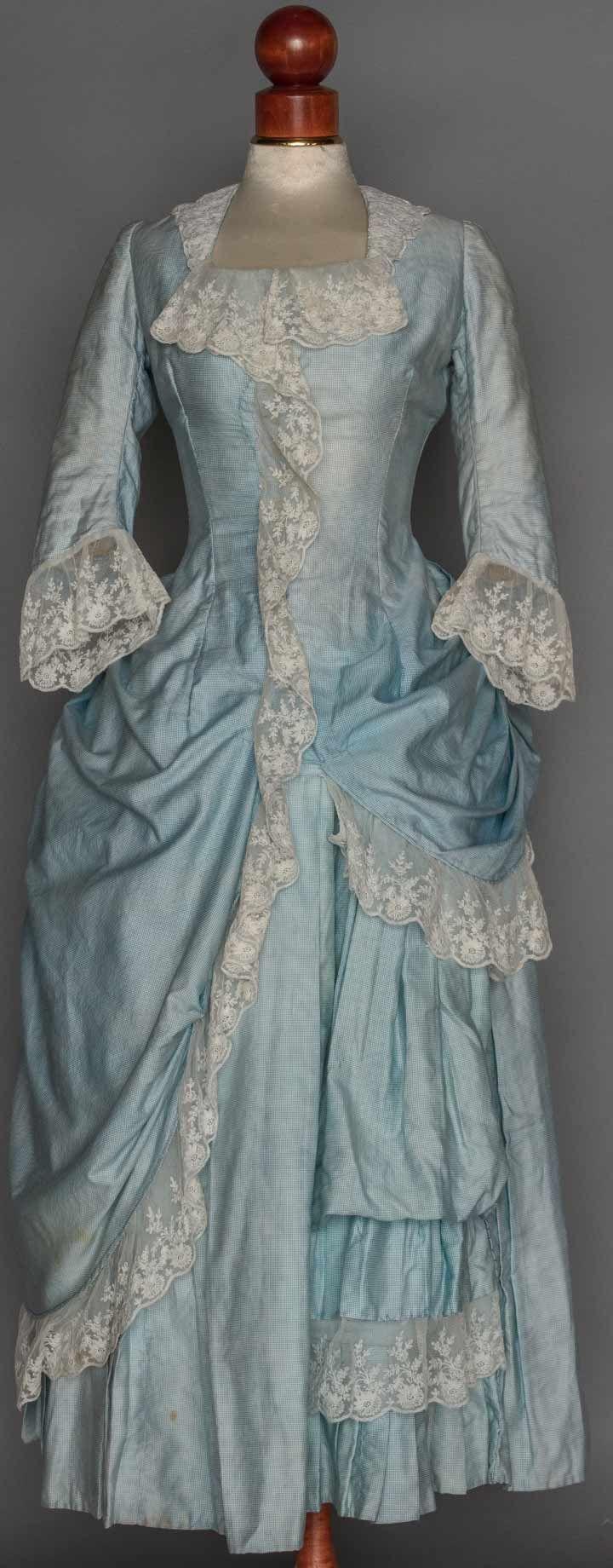 "1-piece navy silk satin, bodice & bustle skirt trimmed w/ navy & copper striped ribbon, B 32"", W 23"", L 35""-37"", excellent; 1 2-piece pale blue gingham, a-symmetric polonaise skirt, trimmed w/ lace flounces, B 34"", W 27"", Skirt L 49"", (stains, faded)fair."
