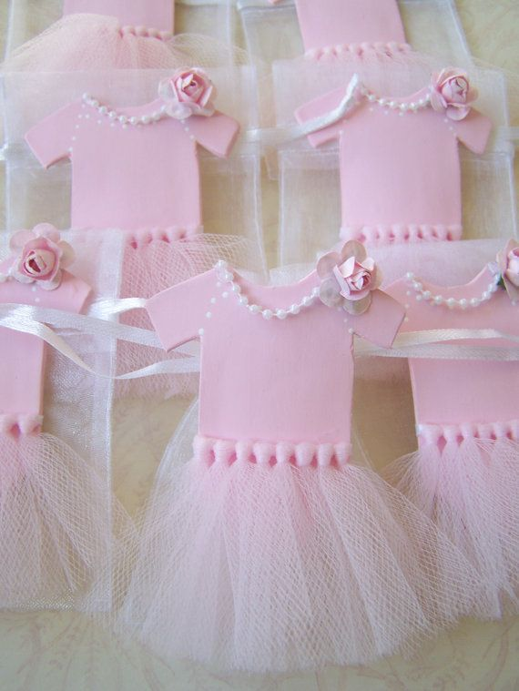 10 pieces are included per order. Beautiful ballerina baby onesie with tutu favor bags. Great for upcoming baby showers or babys 1st birthday. Really feminine party piece. All handmade and exclusive to GirlyBows. Onesie is made using craft porcelain paste. Color is then added to paste to achieve a light pink color. Once allowed to dried the piece is hot glued securely to the organza favor bag. All handmade in light pink shade and finished with a pink colored rose ( pink rose color may vary…