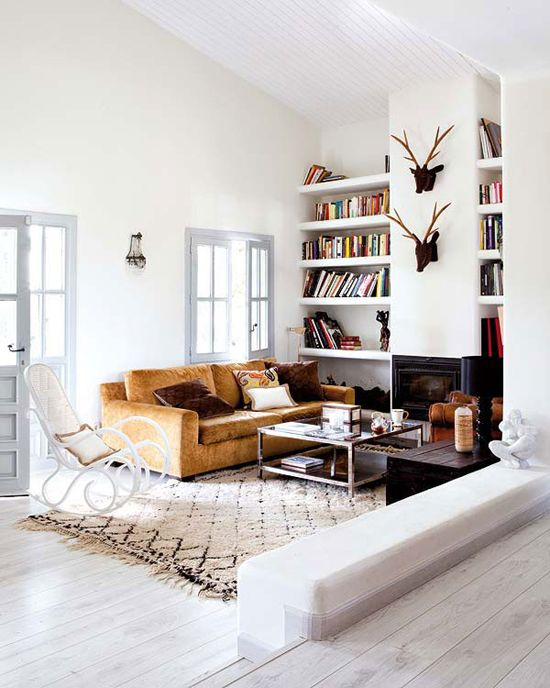 Modern country living room. Fireplace. white walls. Mustard sofa and ercol rocker.