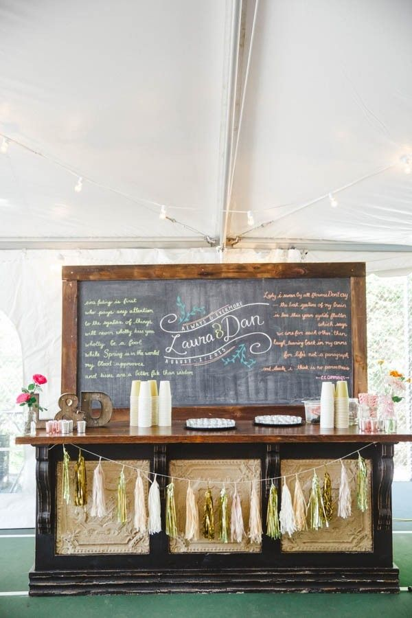 Oversized metallic tassels, a vintage bar, and a chalkboard commanded a major presence at this Ontario wedding! The backdrop featured the couple's favorite love poem and kept it personal by emblazoning a hand-drawn version of their wedding logo in the middle of the chalkboard. Between the petite floral displays and votive candles, we love the delicate touches that pull this epic drink station's style together. Check out more wedding drink stations here…