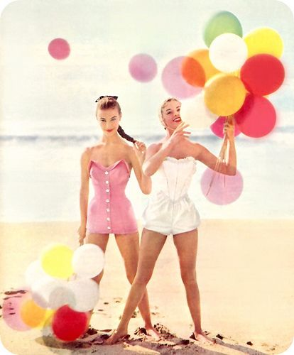 Vintage colourful balloons on the beach with ladies in retro swim wear.