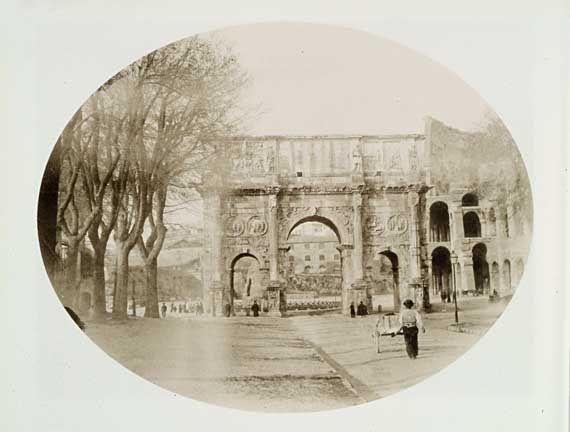 Il lato settentrionale dell'Arco di Costantino in una foto del primo decennio del Novecento, quando fu sistemata la recinzione lignea intorno alla meta Sudans.