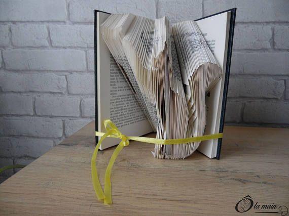 La collection A Livre Ouvert est une série de livres doccasion transformés en objets de décoration via plusieurs techniques (découpage, pliage ou décou-pliage). Chaque page est découpée et/ou pliée à la main pour donner vie à un motif.  Le modèle Une vie de chat est un livre plié pour représenter la silhouette dun chat jouant avec un papillon. Le livre possède une magnifique couverture bleue et or. Sagissant dun vieux livre, la reliure est légèrement abîmé ce qui fait tout son charme!  V...