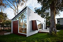 The home built on a native bush site in Northern Tasmania makes a feature of an existing 30-metre gum tree.