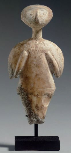 Anatolian marble Kiliya idol, Chalcolitic period, 3300-2500 B.C. The stylized figure with a broad backward tilted head with small protruding eyes and ears and a slender raised nose, the thin elongated neck supported on broad sloping shoulders, folded forearms in relief, the torso delineated from the lower half of the body by a thin incised line across the hips running around the entire figure, three lines defining the pelvic region and legs on the front, 12 cm high. Private collection