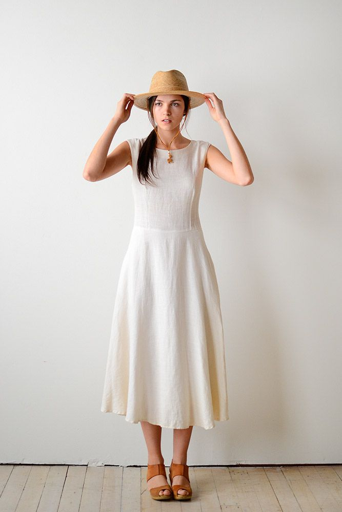 White linen fit-and-flare dress, brown high heel clogs, straw hat