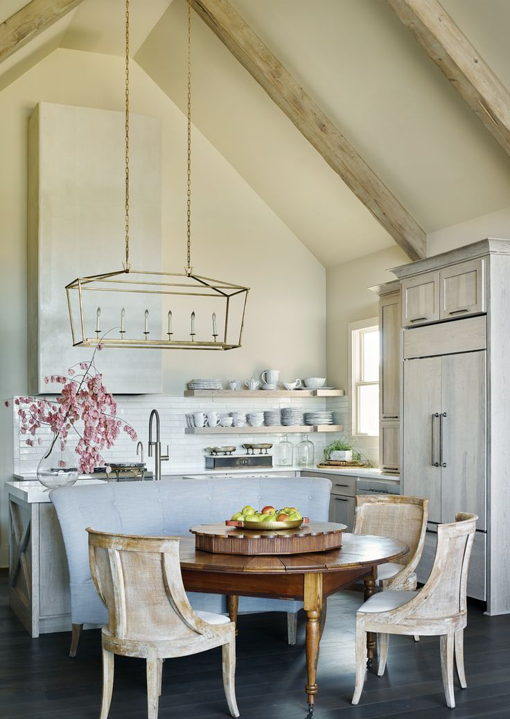 This kitchen may be new, but interior designer Buffy Ferguson gave it the patina of an old Belgian farmhouse, with softly glazed cabinets, open shelves, and ceiling beams in a light finish. The peaceful setting on Lake Roquemore in Newnan inspired a bluish-gray palette resembling the reflection of water.