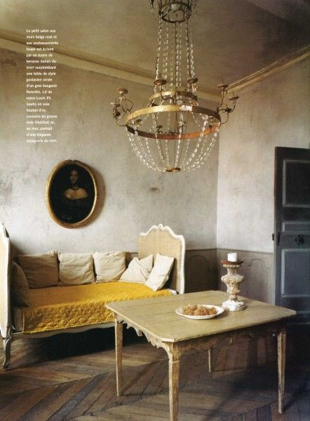 Raw walls coupled with the pop of yellow tied together by the gold chandelier