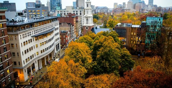 Aerial view of Suffolk Law School building with park showing orange and red leaves in the trees