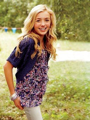 La chica lleva un sueter azul, una camisa rosada y azul, y los jeans blancos.