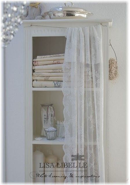 Nice studio storage with pretty lace curtains  (shelving unit or curio with lace curtain)