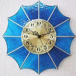 ゴールドの文字盤の周りに扇形のステンドグラスピースを配置して、開いた傘を上から見たような形にデザインしたインテリア時計です。美しい海をイメージしたマリンブルーのステンドグラスを使って製作してあります。美しい色合いで存在感がある掛け時計なので、ご自宅やお店のインテリアにお役立てください。インテリアコーディネートや模様替え時にピッタリです。白い壁に掛けるとステンドグラスの色合いがより美しく映えます。裏側のムーブメントと表側の文字盤は回転するので、二通りの飾り方ができるのも魅力です。詳細説明時計サイズ:275×275mm(15度回転時:265×265mm)ステンドグラスの色:マリンブルー文字盤サイズ:直径125mm文字盤の色:ゴールド、時計針の色:黒ムーブメント:セイコークロック株式会社製クオーツ(平均月差±20秒)(単3乾電池1本使用、電池は付属していません)納期についてこちらの商品は、ご注文後の製作となりますので、発送までに10日前後必要となります。…