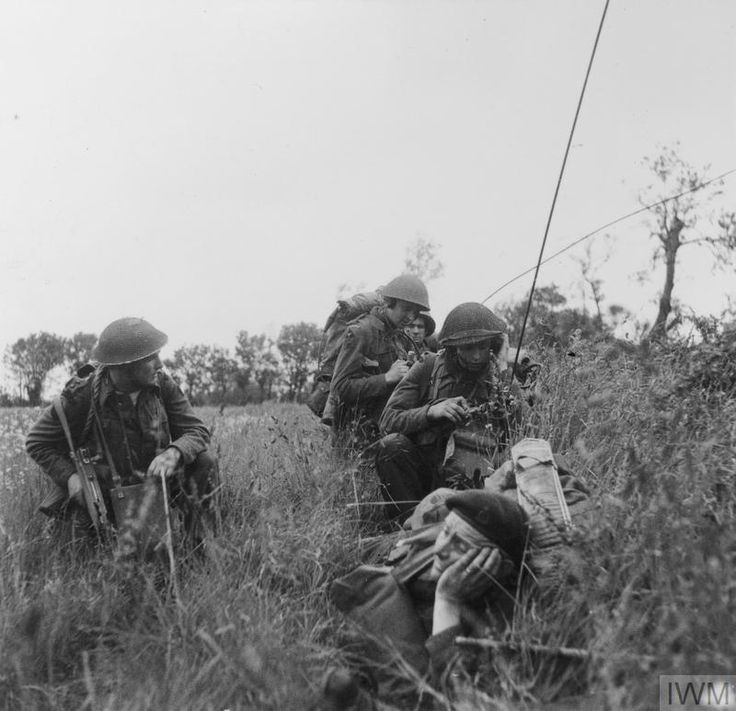 A Commando officer of 1st Special Service Brigade (left) with 3rd Division signallers using man-pack radio sets during the move inland, 6 June 1944.