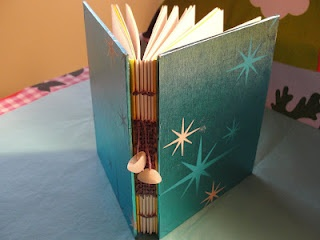 I covered this one with some vintage Christmas wrapping paper. The spine is needle woven and adorned with a few glass beads.
