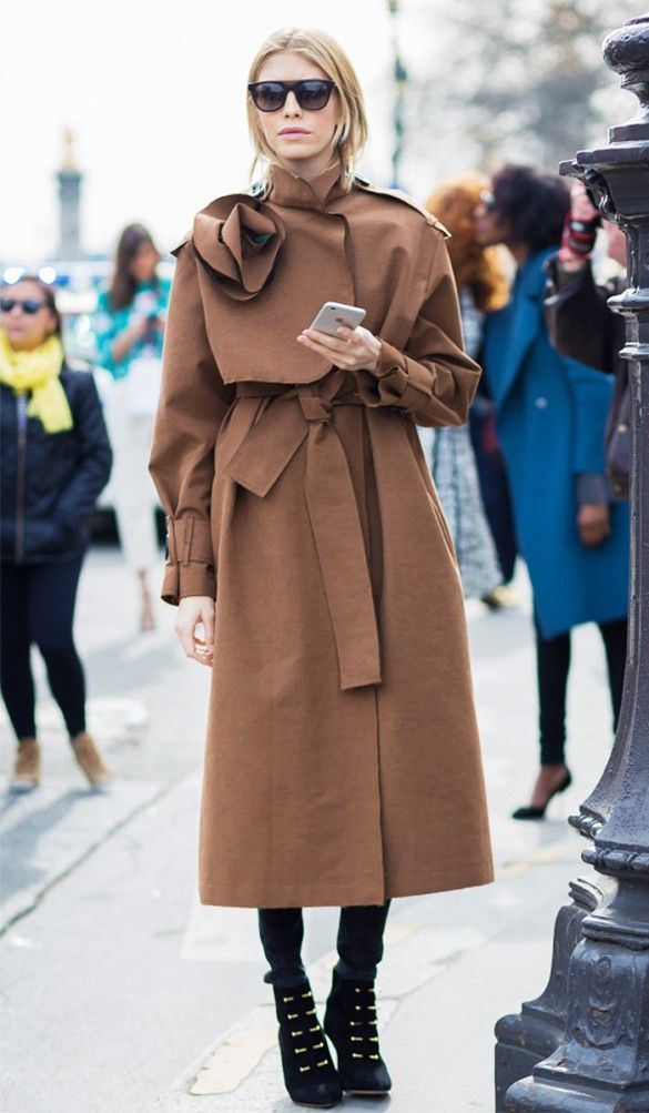 A brown trench coat is paired with black ankle boots.