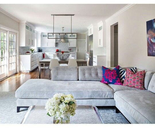 Pinned from NEW YORK based Delano Decor Instagram   mid-century modern design meets hollywood regency glam in this open floor plan home   grey velvet sectional sofa with button-tufted cushions  grey and white interior design   white kitchen cabinets and dining chairs   open concept condo apartment living room kitchen