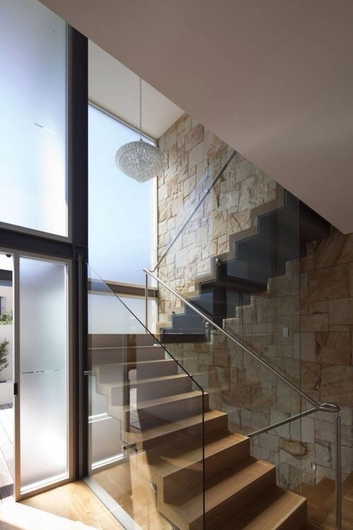 Interior residential architecture: wooden staircase with glass balustrade frosted glass window, sandstone wall (mw)