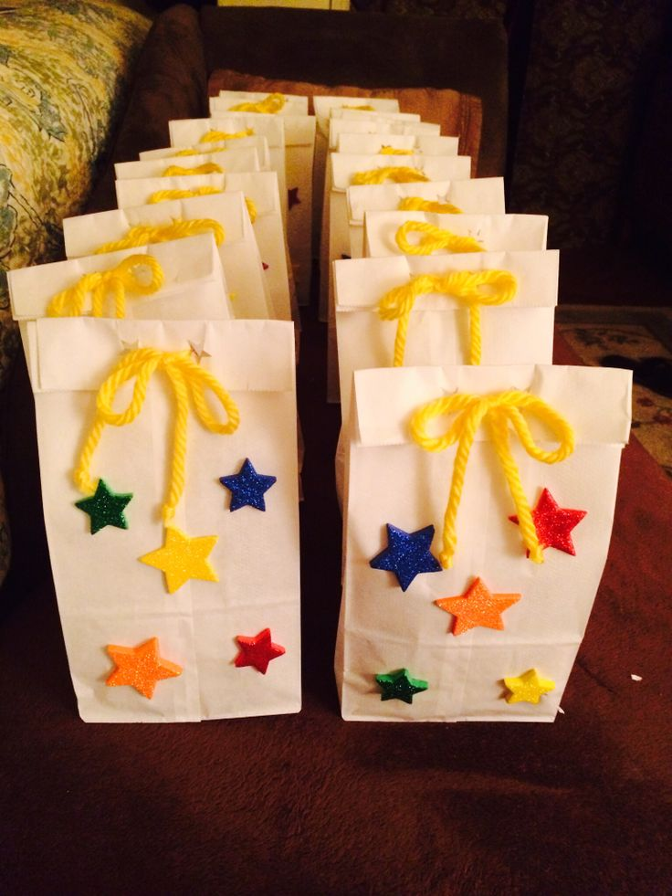 School gift bags! I made them for my daughters' end of the year party! You can fill them with goodies. These have a kool-aid jammers juice, fruit roll up, smarties, tie dye shape rubber bands, cute key chain,  and a popcorn packet in each bag.    White paper lunch bag Star shaped foam stickers  Star hole punch  Yellow twine  Very easy to make and inexpensive!
