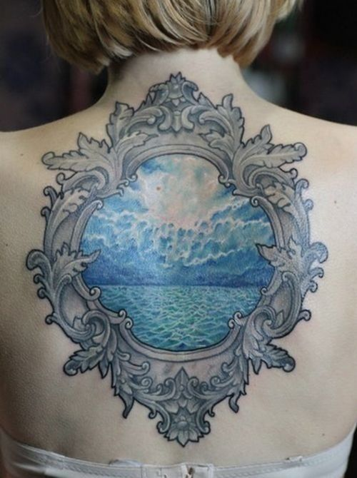 Black and grey ornate frame design tattoo with shaded blue sky and ocean inside.