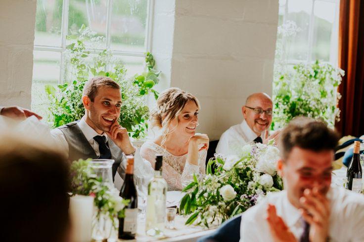 The wedding party enjoying the speeches in Wytham Village Hall, Oxfordshire. Photo by Benjamin Stuart Photography #weddingphotography #speeches #light #wytham #ukwedding #villagehallwedding #flowers #smile