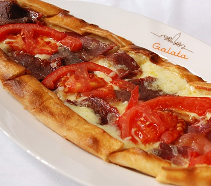 Turkish pide with pastrami, tomato and cheese