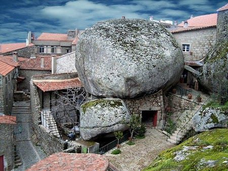 "This extrodianry place is the town of Monsanto in Portugal. The homes as you can see are built around and into giant boulders. The town was named ""the most Portuguese village in Portugal"" in 1938 and has building restrictions to ensure it is not developed upon."