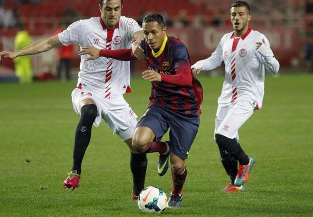GRA334. SEVILLA, 09/02/2014.- El defensa brasileño del FC Barcelona Adriano Correia (c) es agarrado por el centrocampista del Sevilla FC Vic...