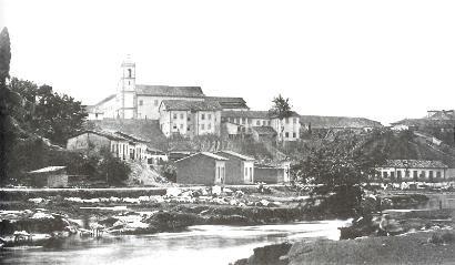 O Rio Tamanduateí correndo ao lado da Rua 25 de Março; ao fundo, o mosteiro de São Bento. Foto de Militão Augusto de Azevedo, c.1862