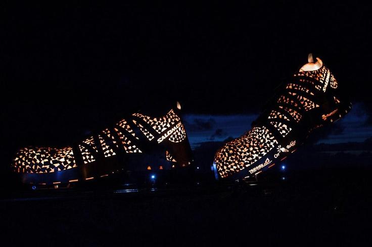 Fjoertoer 2012 Terschelling. Verbeelding van 'Het vuur uit de sloffen' voor wandelevenement de Fjoertoer. Op het strand zien deelnemers aan de tocht, die in het donker over het strand gaat, reusachtige sportschoenen lopen.  Ontwerp en constructie: Cor Bakker en Henk Trip.