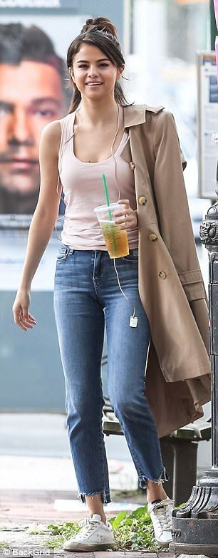 Iced-tea fan: The minimally-made up former Nickelodeon starlet was wearing a pink tank top beneath her coat and she scraped her brunette bob into a partial updo