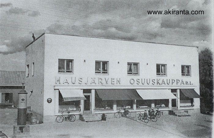 Hausjärven Osuuskauppa. Vuonna 1935 valmistui tiilestä rakennettu funkkis -tyylinen liiketalo. Liikkeen nimi vaihtui 1927 Hausjärven Osuuskaupaksi. Yläkerrassa on asuinhuoneisto. Kauppareissu taittui yleensä polkupyörällä, autoja ei vielä ollut paljon. Korkea bensapumppu vasemmalla.