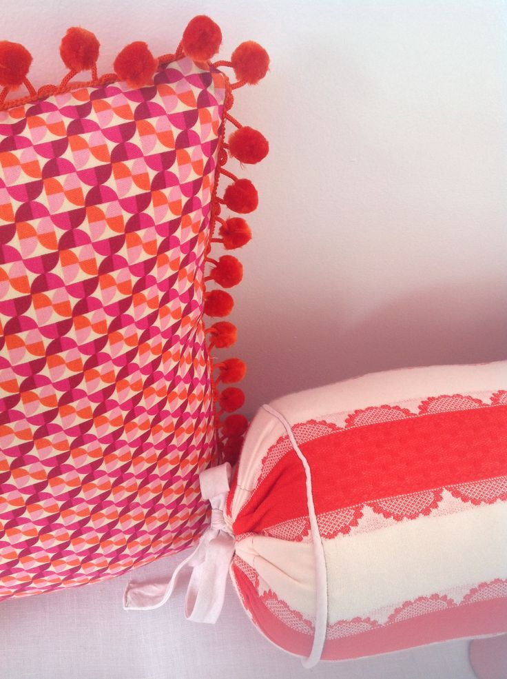 Homemade cushions and squab in orange, red, and pinks... Lots of patterns, Pom Pom trims, etc. to give a soft retro / vintage look.