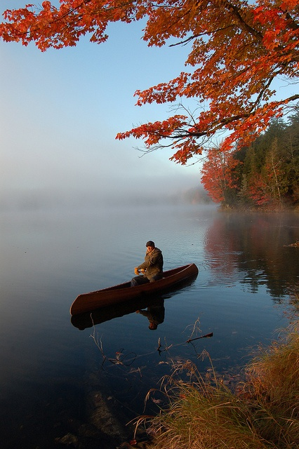 Crisp fall air, mist rising from a calm lake and red maple leaves frame this lovely scene of the canoeist on Mountain Lake in the Sylvania wilderness Area near Watersmeet, Michigan