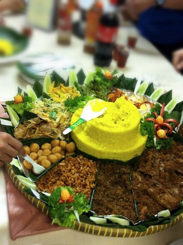 Nasi tumpeng: On several special events, nasi kuning is shaped into a yellow cone popularly known as nasi tumpeng, served on a tampah with an assortment of side dishes. The lopping off of the tumpeng's top often symbolizes the event's celebration. (Photo by Angga Suryokusumo)