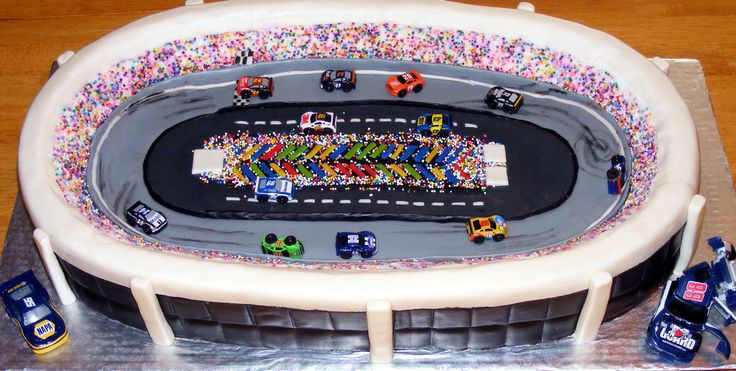 Nascar Cake - Chocolate Cake and Icing, 2 13x9 cakes side by side, carved into shape, rice krispie stands, fondant decorations and nascar toy cars.