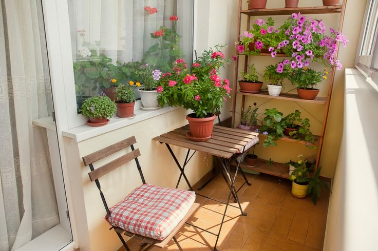 Balcony with small table, chair and flowers.