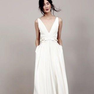 Schlicht und elegant: ärmelloses Brautkleid mit tiefem V-Ausschnitt und Taillengürtel mit Schleife und Schnallen von Kaviar Gauche.