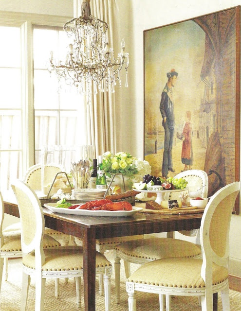 """Seaside painting and crystal chandelier, both 19th-c. French. Oly side chairs in raffia around oak table from Old Timber Table Co."" Dallas, Texas, home of designer Lisa Luby Ryan and her sailor husband, Jay Ryan. Interior design by Lisa Luby Ryan. Photo: Aimee Herring. ""Welcome Glow."" Veranda (2008)."