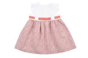 Vestido para bebe niña en color blanco y con la falda estampada de florecitas rojas. Cuello redondo y sin mangas, con un vuelito plisado en el borde.