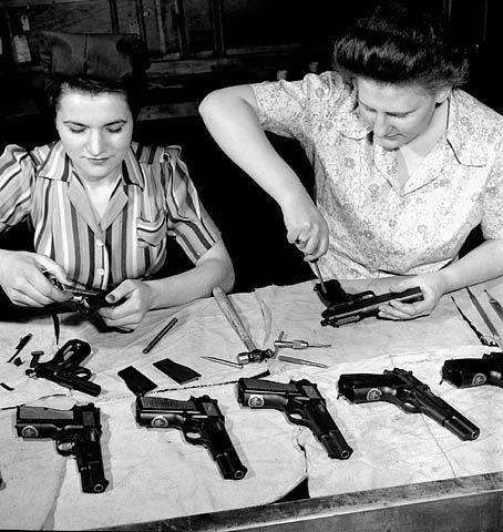 Workers assemble Browning-Inglis Hi-Power pistols at the John Inglis munitions plant, Canada, April 1944.  The Hi-Power is one of the most widely used military pistols of all time,having been used by the armed forces of over 50 countries. Designed by John Browning, the Hi Power was completed by the Belgian firearms firm of  Fabrique Nationale (FN) of Herstal, Belgium. Accurate, robust and with a 13-round magazine, the Hi Power is still in production and has spawned many current variants.