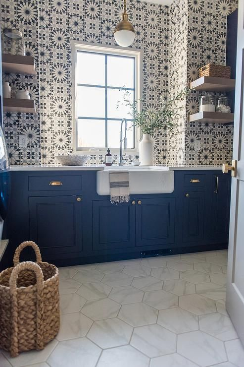 White hex floor tiles contrast navy blue shaker laundry room cabinets accented with brass hardware and a white countertop holding a farmhouse sink with a stainless steel pull out faucet.