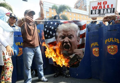 Photos of the day - February 4 2017Protesters burn a portrait...  Photos of the day - February 4 2017  Protesters burn a portrait of U.S. President Donald Trump during a rally at the U.S. Embassy in Manila Philippines; a Ukrainian fighter of the Right Sector battalion stands in a building damaged by shelling in Avdiivka Ukraine; a migrant warms himself around a fire in an abandoned warehouse where he and other migrants took refuge in Belgrade Serbia; Pope Francis a crying baby during an…