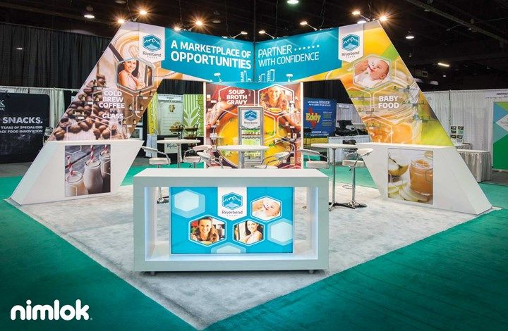 This vibrant 20' x 30' island exhibit features an eye-catching slanted backwall structure, which incorporates SEG fabric graphics, extrusion frame and laminate counters. Clear plex shelving showcases products in an organized and stylish way throughout the exhibit. A welcoming counter gives the booth a focal point, while a comfortable seating area encourages interaction. #display #booth #tradeshowdisplay #tradeshowbooth #tradeshowexhibit