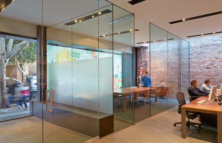 Behind a colorful graphic window there is a conference room divided from the lobby and the main room with entirely glass walls