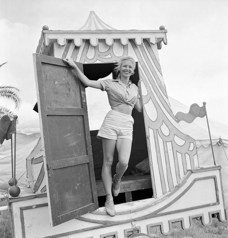 A circus girl standing at a door of a circus vehicle during a rehearsal for the Ringling Bros. and Barnum & Bailey Circus in Sarasota, FL in 1949.