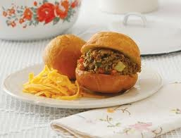 Vetkoek Recipe:   Fill it with a little curried ground beef and some cheddar cheese, or cheese and syrup.  It is basically deep-fried bread that is shaped like a bun. #vetkoek #recipe #southafrica #cooking #food