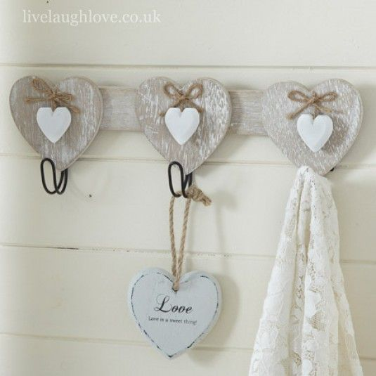 This is a wooden wall hook which has 3 hooks which are attached to wooden hearts and has a country feel about it, This has 3 white wooden hearts that dangle down the front on the front of each heart with a jute bow tied up. This would look good in your country kitchen holding your tea towels.