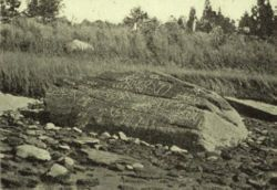 """Dighton Rock - is a 40-ton boulder, originally located in the riverbed of the Taunton River at Berkley, Massachusetts (formerly part of the town of Dighton). The rock is noted for its petroglyphs (""""primarily lines, geometric shapes, and schematic drawings of people, along with writing, both verified and not.""""),[2] carved designs of ancient and uncertain origin, and the controversy about their creators..."""