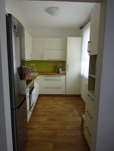Zelené obklady za pracovním pultem kuchyň hezky rozveselily.